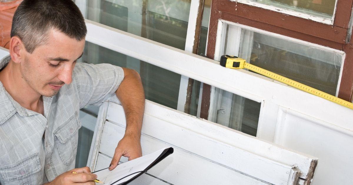 un serramentista prendere le misure delle finestre