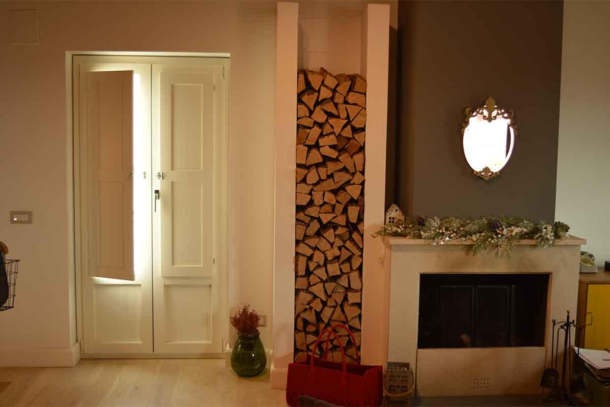 un'abitazione stile rustico con caminetto, legnaia e infisso in alluminio effetto legno bianco per balcone, dotato di scuri interne