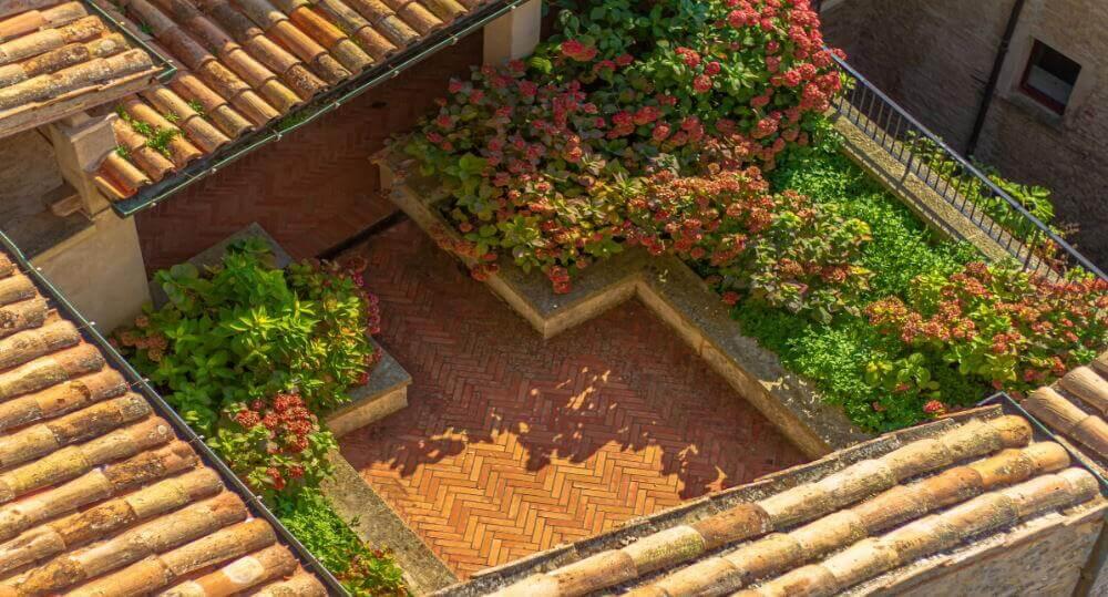 balcone fiorito ricavato su una terrazza ad asola all'ultimo piano di un palazzo del centro storico
