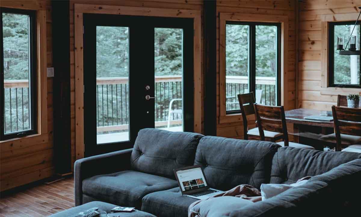 Colore infissi alluminio caldo e scuro in un soggiorno con divano in stile classico scuro