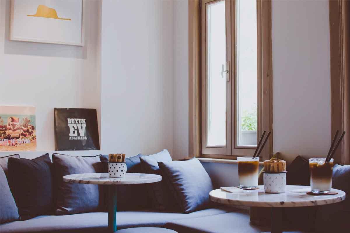 un soggiorno moderno con divano blu e infissi salvaspazio per le finestre effetto legno