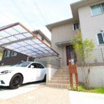 automobile parcheggiata sotto un carport per auto, la tettoia è trasparente e le finiture sono in alluminio color legno