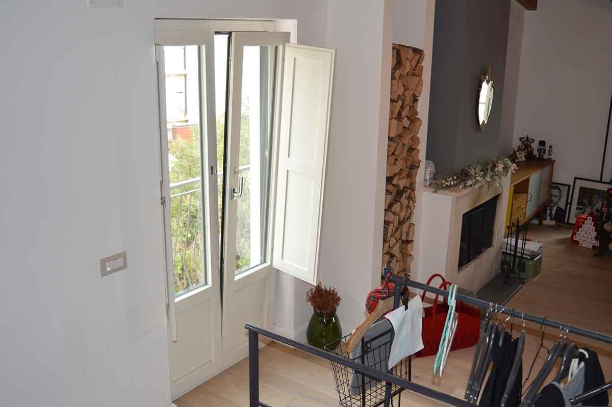 casa stile rustico con caminetto, legnaia e infisso in alluminio effetto legno basculante per il balcone